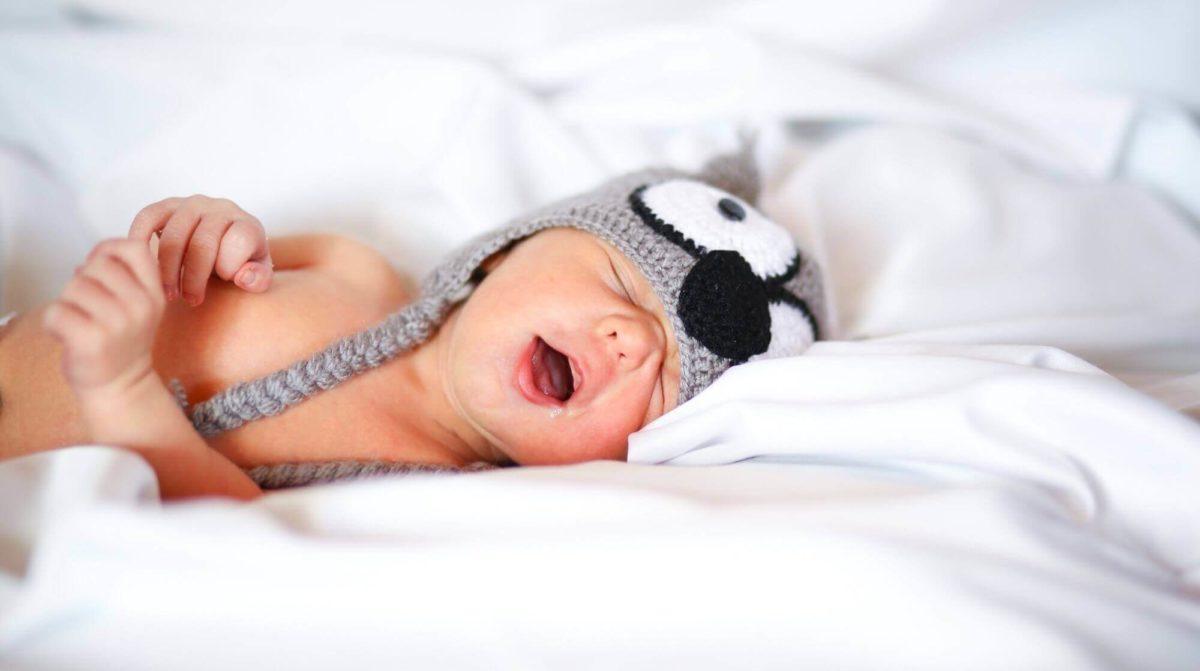 baby die op bed ligt