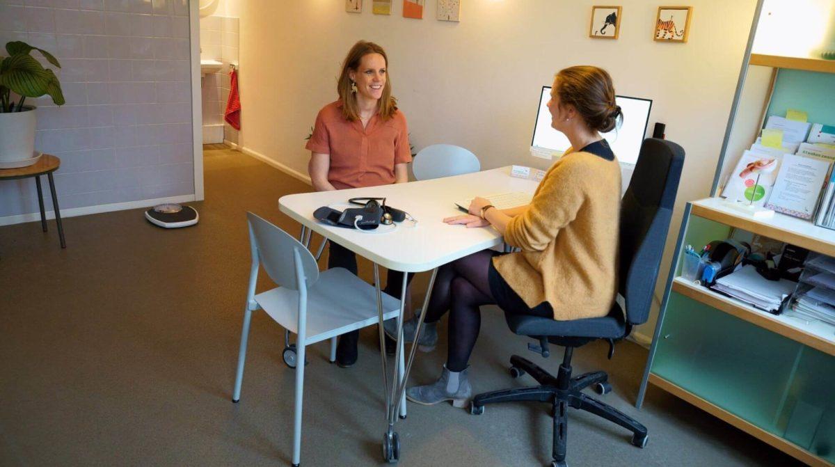 zwangere vrouw heeft gesprek met medewerkster